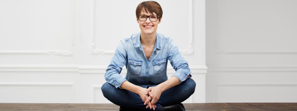 Porträt Nadja Katzenberger im Schneidersitz vor weißem Hintergrund